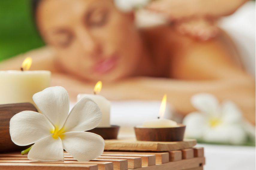 woman enjoying a massage with three lit flowers and flower petals